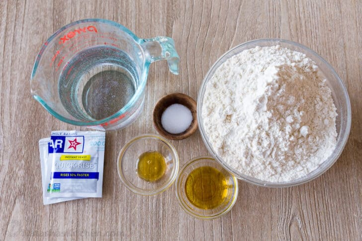 Ingredients for Italian focaccia with flour, yeast, salt, honey, water and olive oil