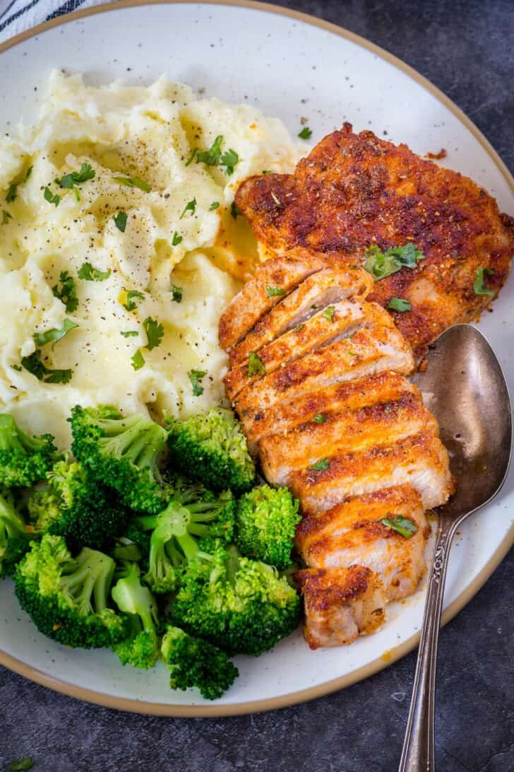 Mashed potatoes, broccoli and air fryer pork chops on a white plate with a metal spoon.