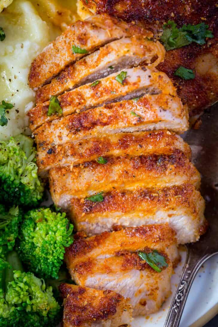Juicy pork chop cut into slices topped with fresh greens.