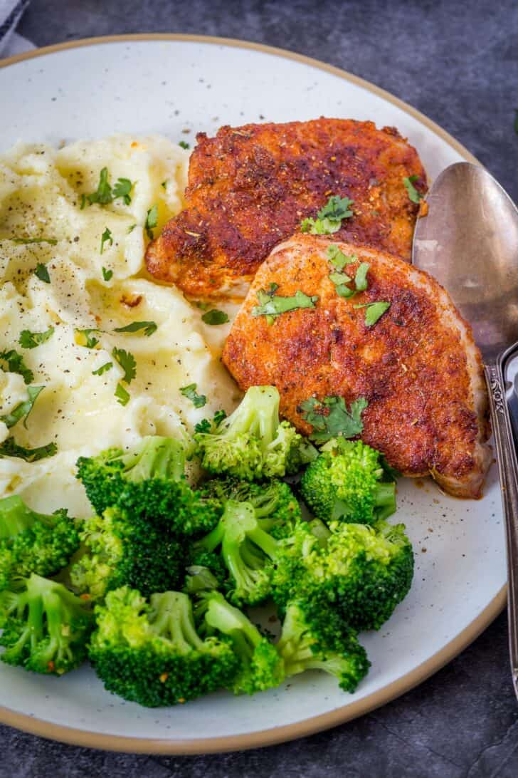 Pork chops in a plate with broccol and mashed potatoes topped with fresh greens.