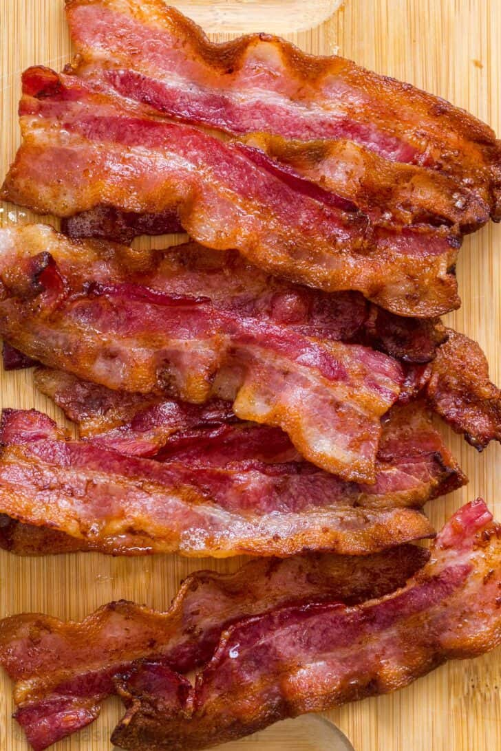Crispy cooked bacon laid out on a cutting board.