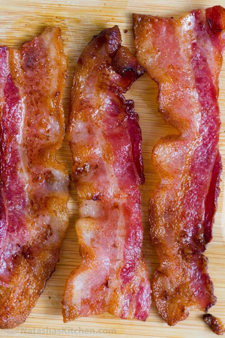 Three slices of crispy cooked bacon laid out on a cutting board.