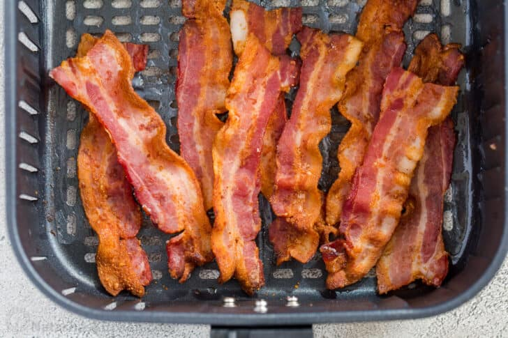 Crunchy bacon strips laid out in an air fryer basket.