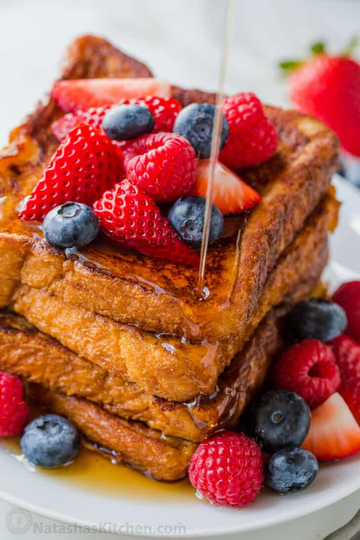 Stacked french toast drizzled with maple syrup and topped with berries