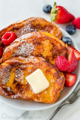 French Toast Slices on a plate with butter and maple syrup