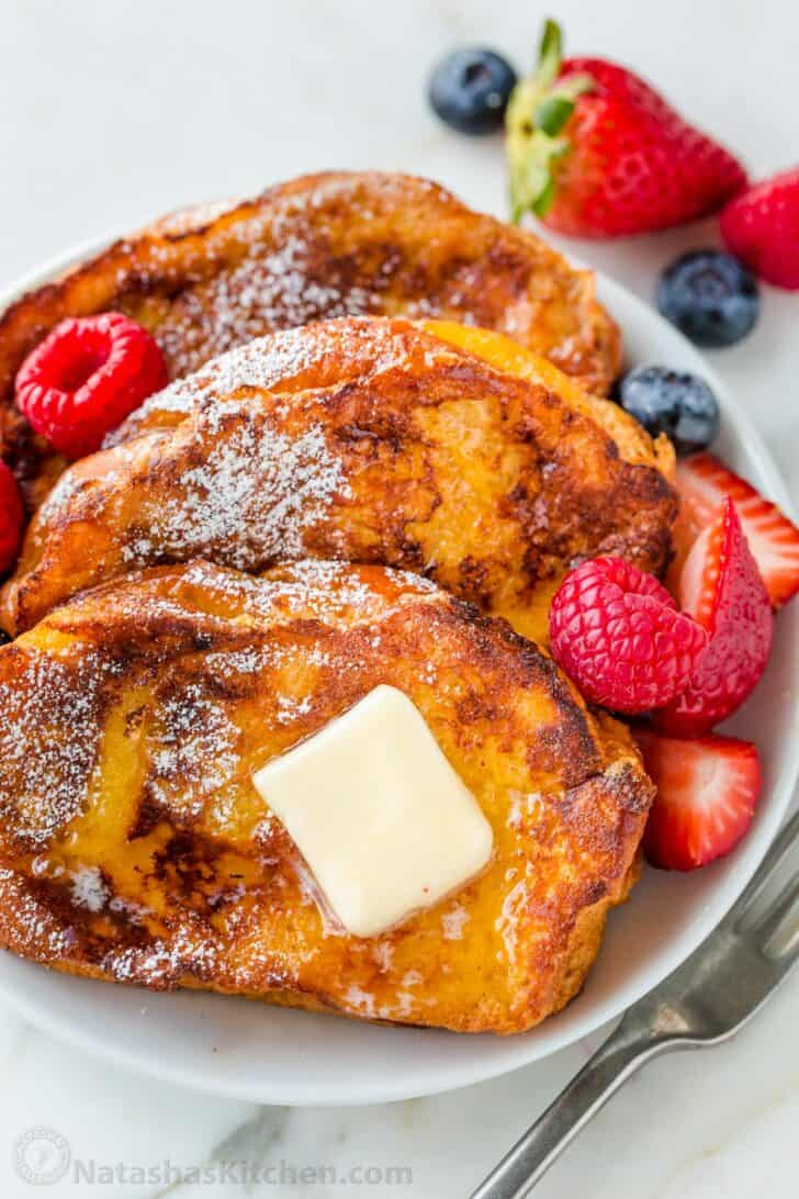 French Toast on a plate served with butter, powdered sugar and maple syrup