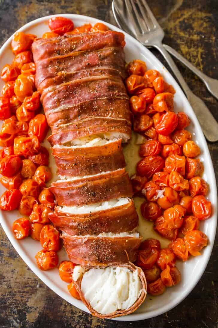 A plate with roasted cod wrapped in prosciutto with cherry tomatoes