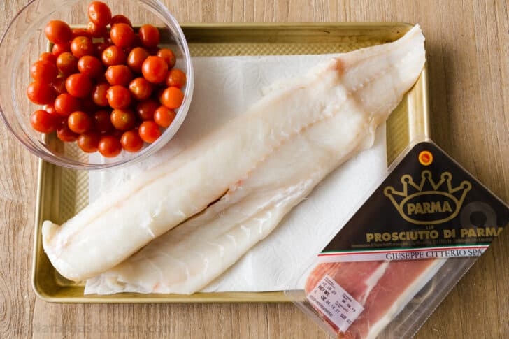 Wild Cod filet on baking sheet with tomatoes and prosciutto