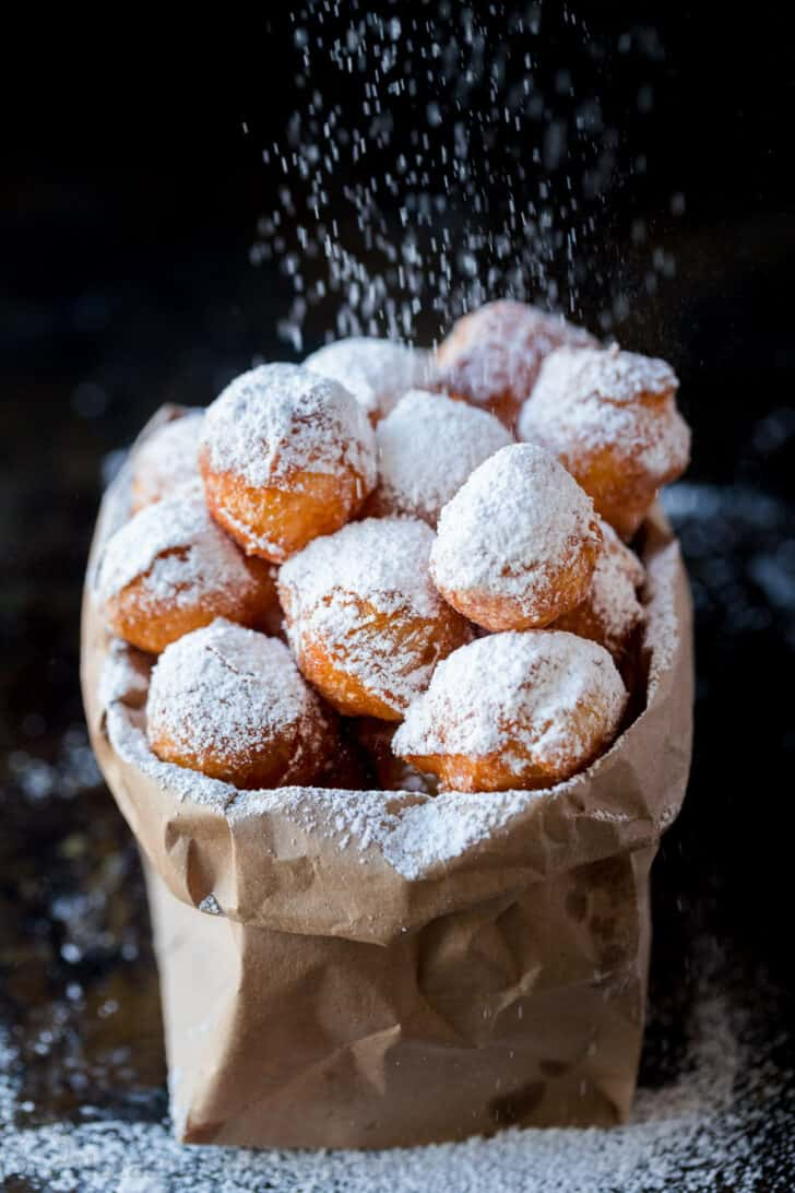 Zeppole in paper bag dusted with powdered sugar.