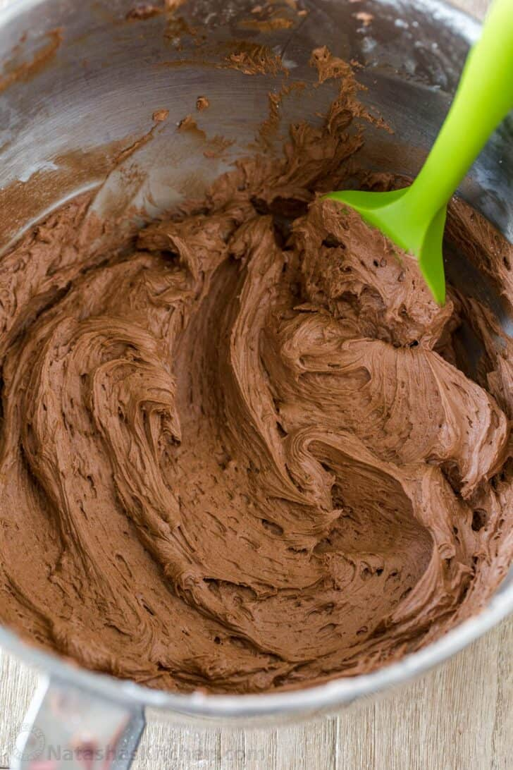 Chocolate Frosting in mixing bowl with green spatula