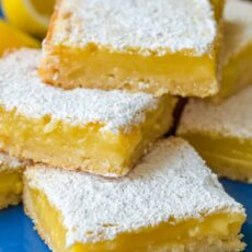 Lemon bars stacked on blue plate