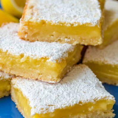 Lemon bars stacked on blue plate