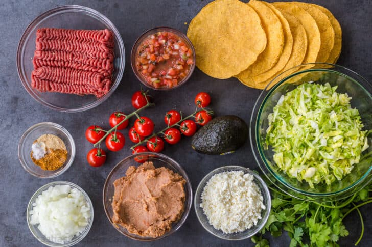 Tostada ingredients with tortillas, refried beans, ground beef and lettuce