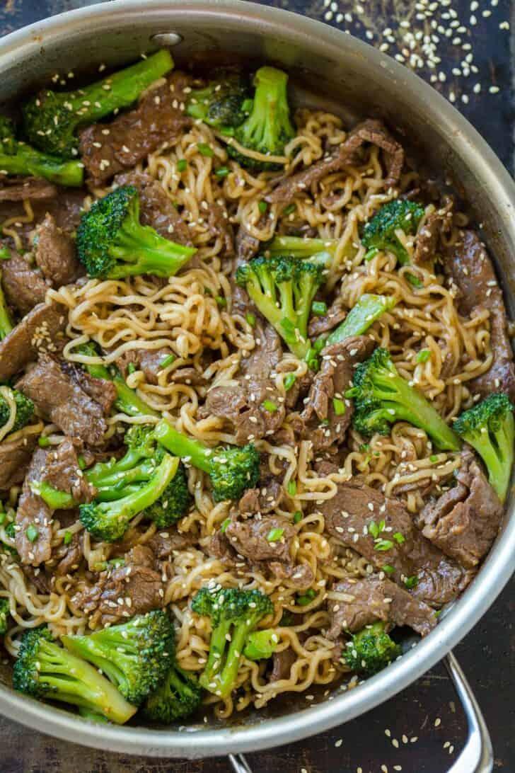 Beef and Broccoli ramen stir fry in skillet garnished with sesame seeds