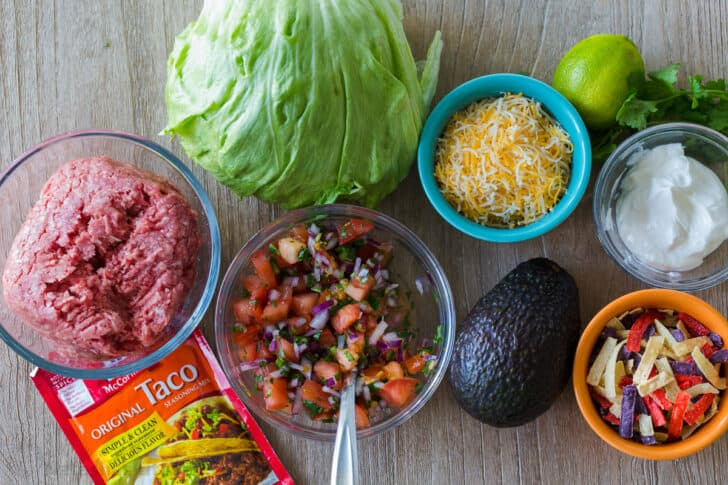 salad ingredients with lettuce, ground beef, taco seasoning, pico, cheese, avocado