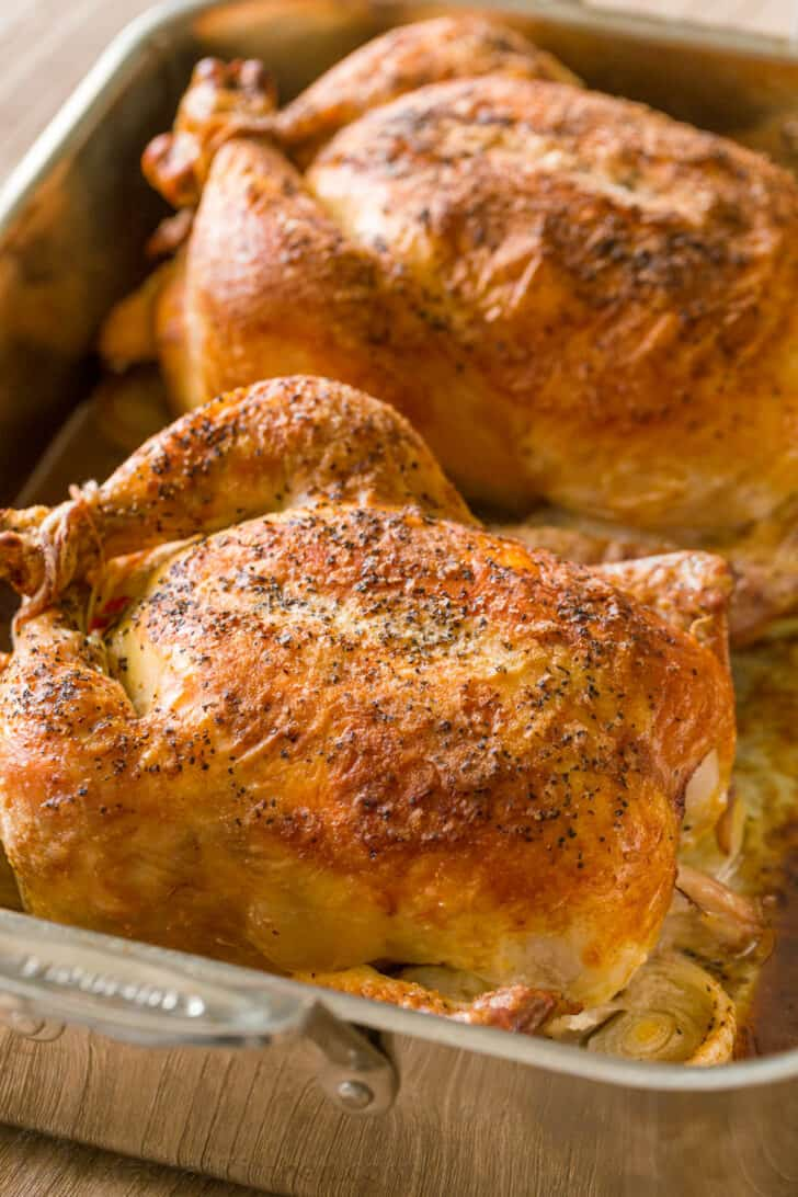 Two whole roasted chickens in a roasting pan