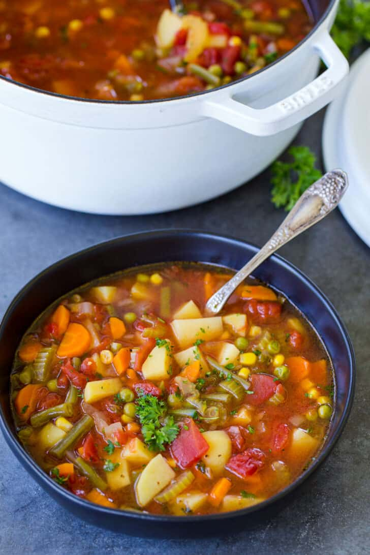 A bowl of vegetable soup next to the pot