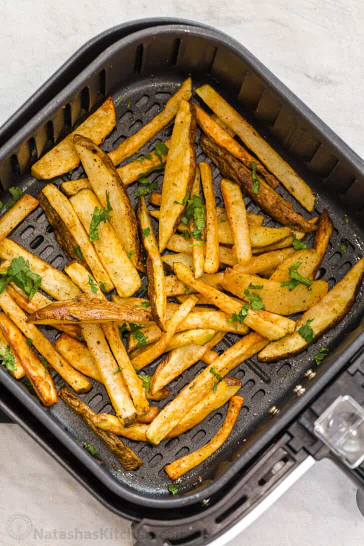 Crispy French fries in an air fryer basket topped with fresh greens.