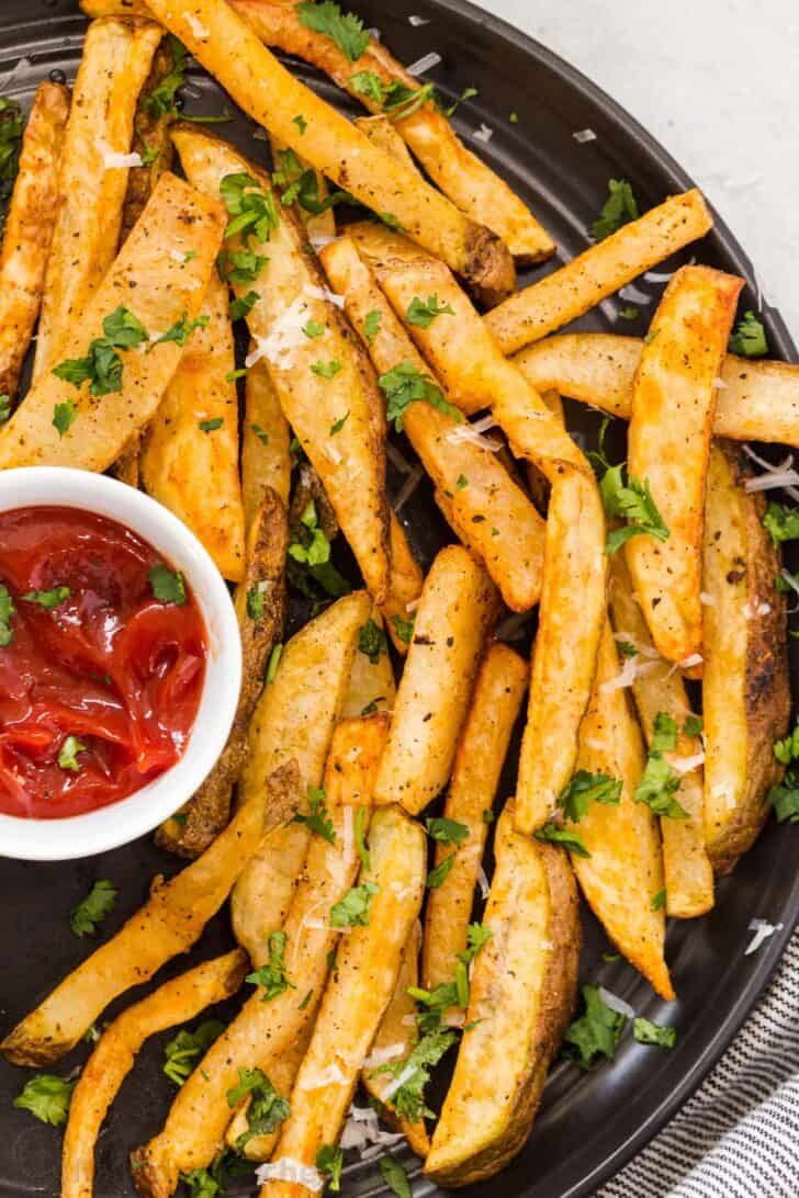 Homemade air fryer French fries on a black plate with a bowl or ketchup.