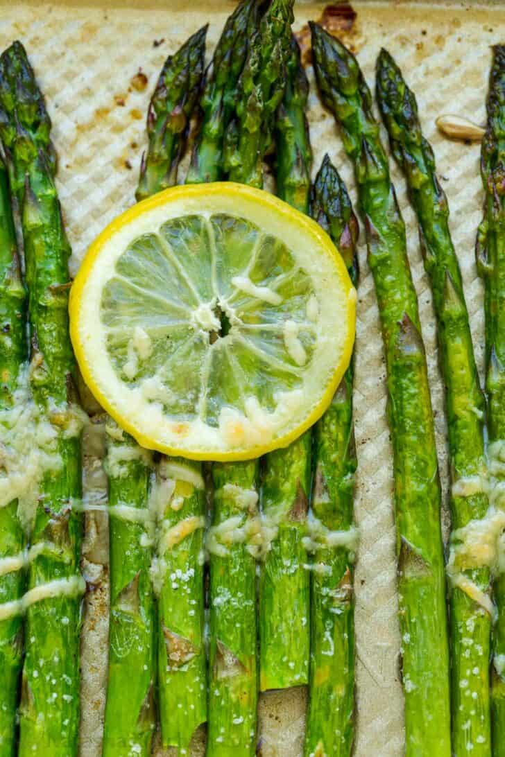 Baked asparagus with slice of lemon and melted parmesan cheese