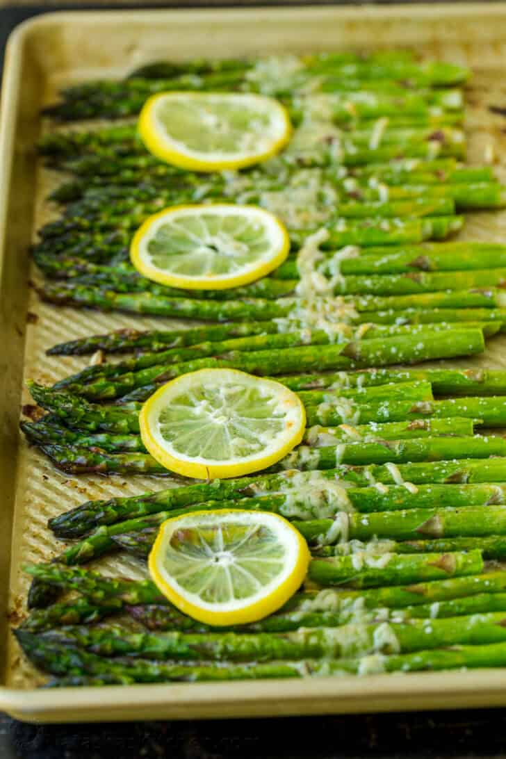 Roasted asparagus on baking sheet with lemon and parmesan.