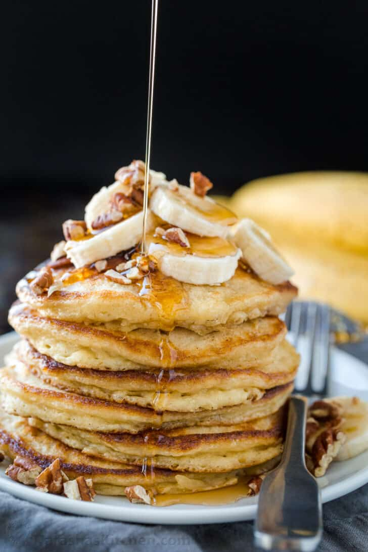 Stack of banana pancakes drizzled with maple syrup