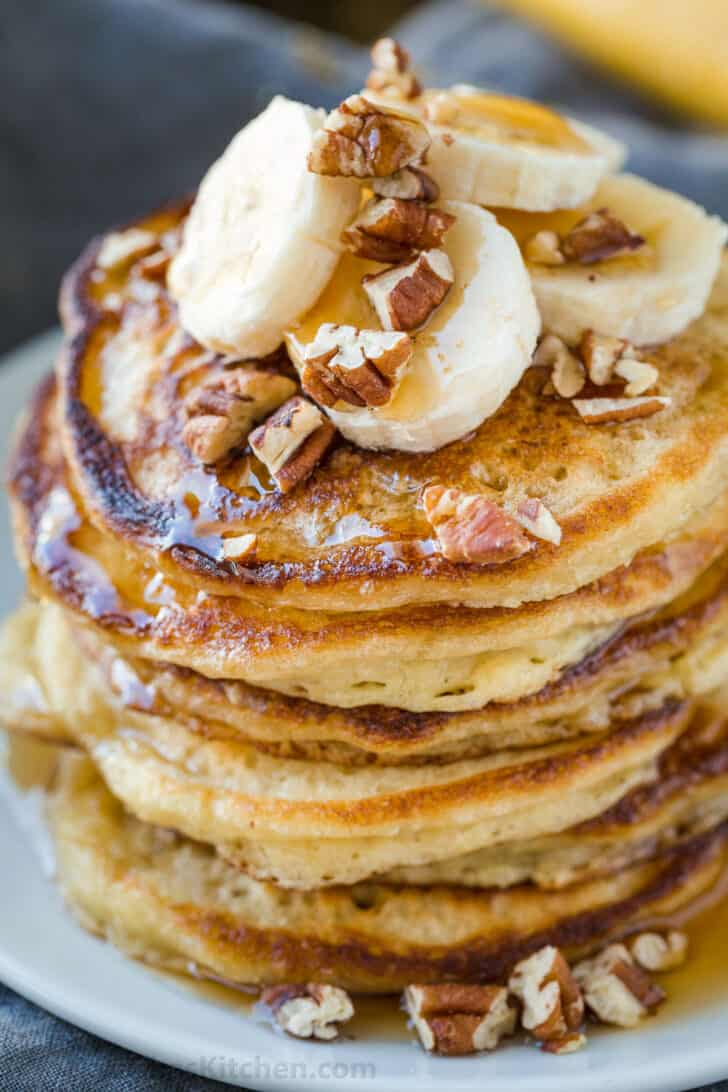 Stacked banana pancakes topped with bananas, pecans and maple syrup