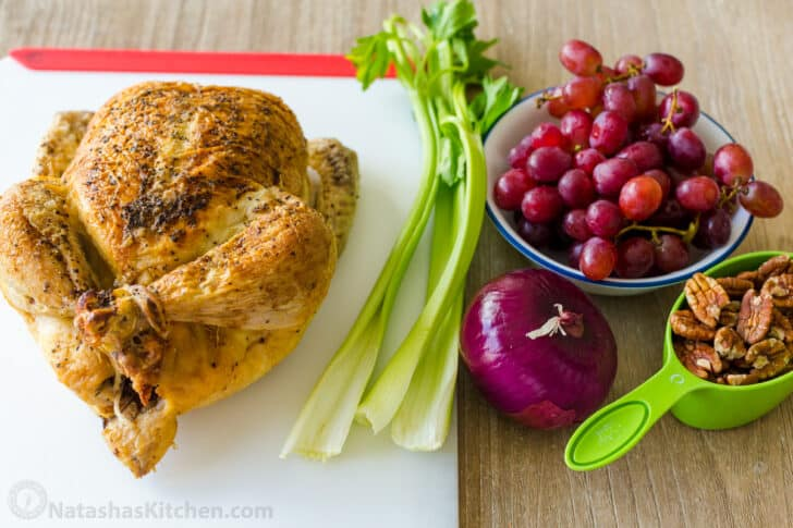 Ingredients for making chicken salad with roasted chicken, celery, grapes, pecans and onion