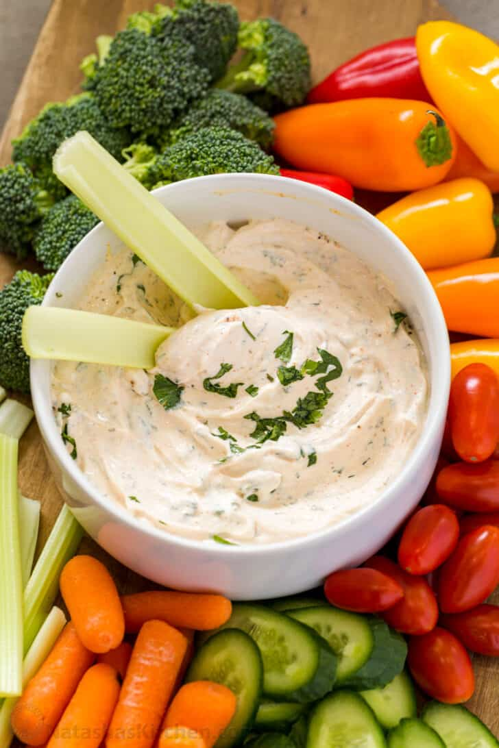 Veggie dip with celery in the dip and fresh vegetables arranged.