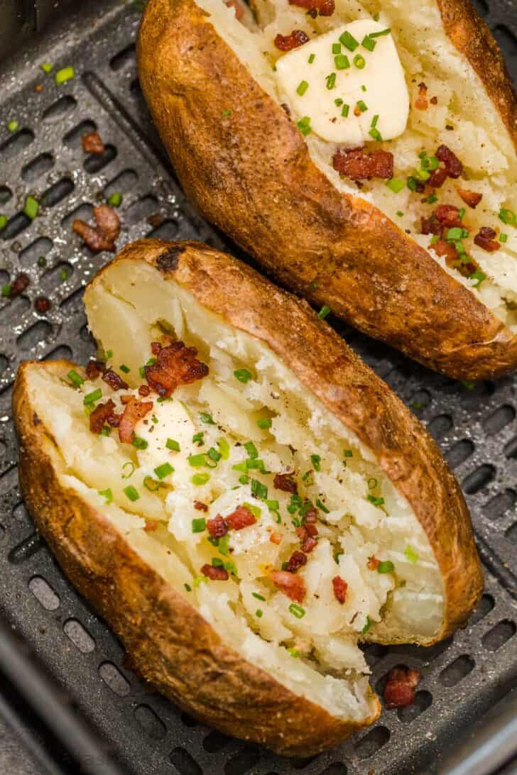 Air fryer baked potatoes topped with butter, bacon, and chopped greens.