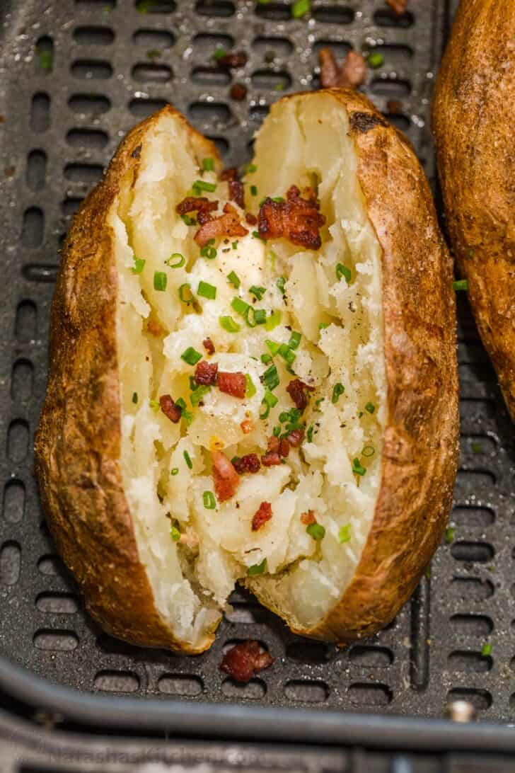 Baked potato loaded with butter, bacon, and green onion in an air fryer basket.