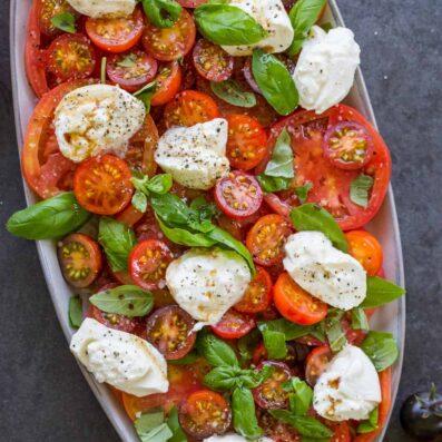 Burrata Salad with tomatoes on platter