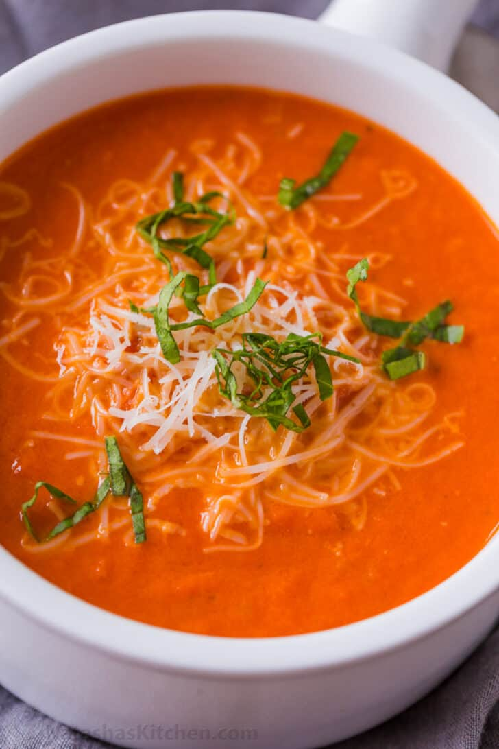 Bowl of creamy tomato soup garnished with parmesan and basil