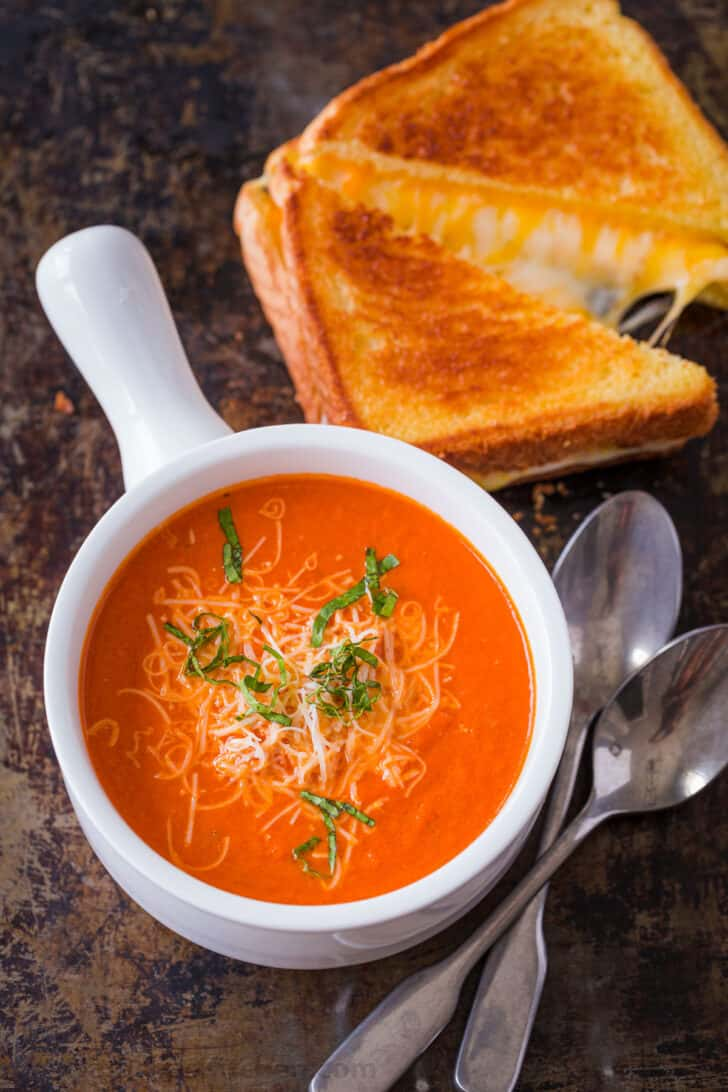 Creamy tomato soup served with grilled cheese sandwich