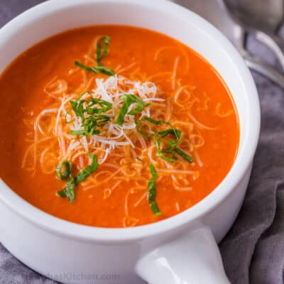 Creamy tomato soup garnished with cheese and basil