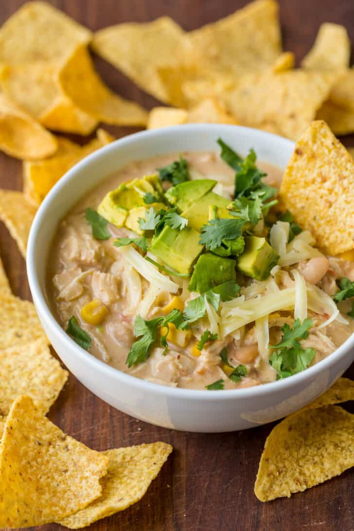Chicken chili served with cheese, avocado and tortilla chips