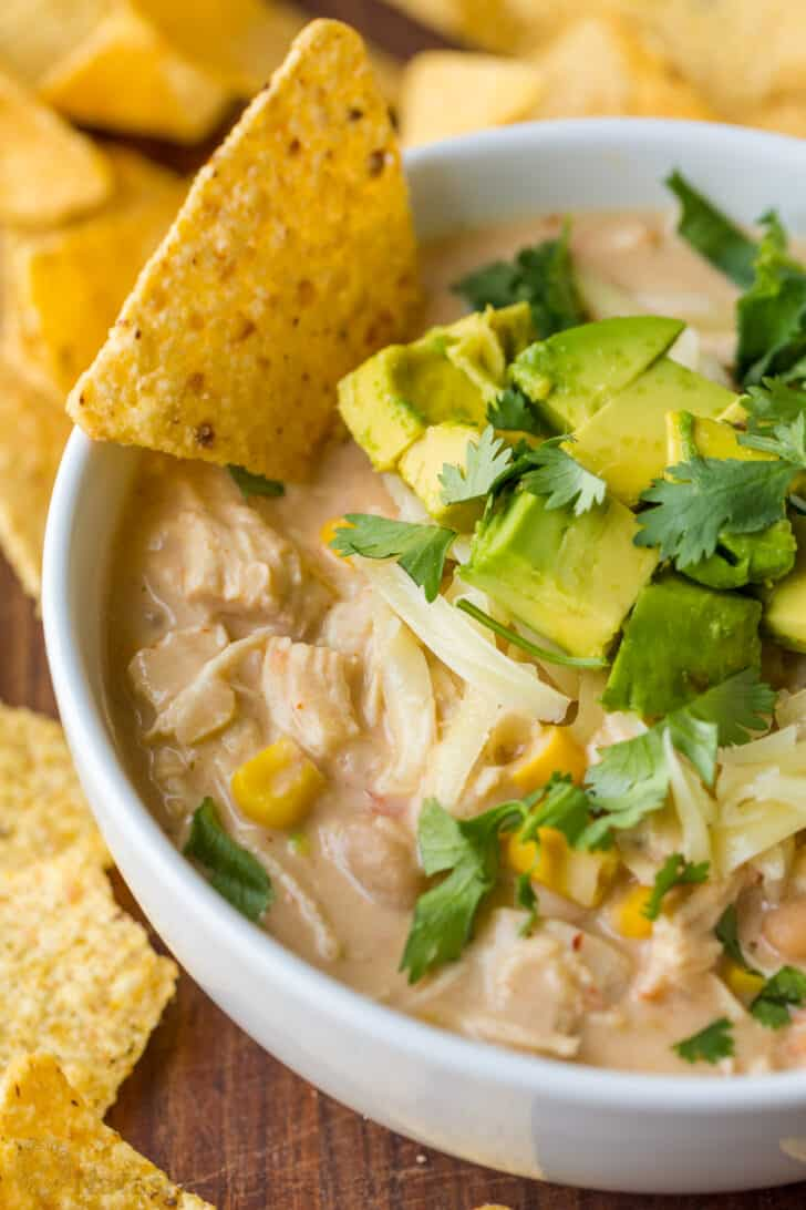 Chicken chili recipe in a bowl served with a tortilla chip and toppings